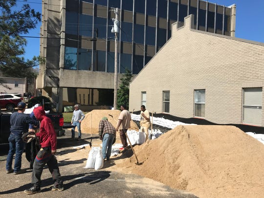 Several businesses on Leila Drive in Jackson work together with help from Henderson Construction to build a protective wall of sandbags around their offices. Friday, Feb.14, 2020.