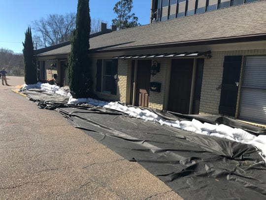 Several businesses on Leila Drive in Jackson work together with the help of Henderson Construction to build a protective wall of sandbags around their offices. Friday, Feb.14, 2020.