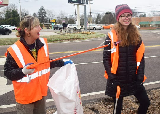 Keep Knoxville Beautiful volunteer Valerie Coleman finds a comb and can't help but tease UT student Elizabeth Baker with it during the Karns Cleanup Saturday, Feb. 8.