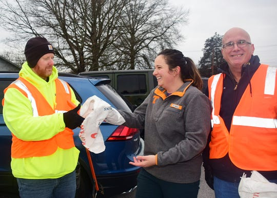 Joshua Boling, left, and Roger Kane, right, get set up with recycled trash bags and tongs from Maddy Staff of Keep Knoxville Beautiful during the Karns Cleanup Saturday, Feb. 8.