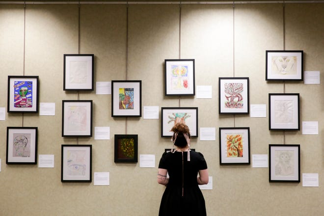 "Art from domestic violence survivors hangs on a wall during an opening reception for YWCA's ""Expressions: Survivors Gallery,"" Thursday, Feb. 13, 2020 at the West Lafayette Public Library in West Lafayette."