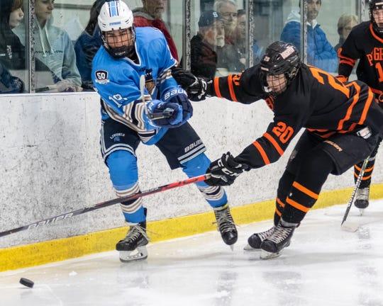 Brighton's Nate Przysiecki (20) and Livonia Stevenson's Jake Smith battle for the puck in the KLAA hockey championship game on Thursday, Feb. 13, 2020 at Eddie Edgar Ice Arena.