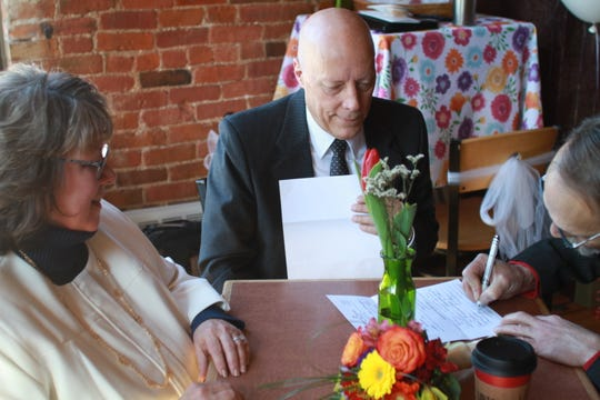 Thomas Walker, 56, from Ann Arbor, signs an official wedding certificate as his now-wife, Denise Morgan, 58, from Brighton, and wedding officiant Bill Fenton, look on.