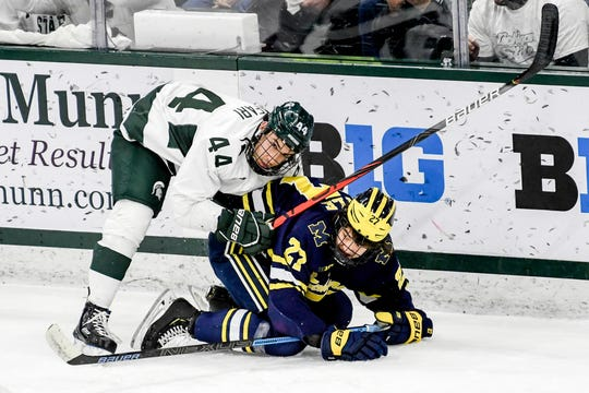 Michigan State's Butrus Ghafari, left, pushes Michigan's Nolan Moyle during the first period on Friday, Feb. 14, 2020, at the Munn Ice Arena in East Lansing.