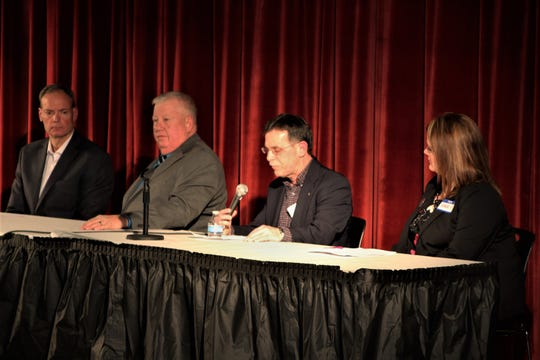 Crawford County Board of Commissioners candidate Larry Schmidt, holding microphone, delivers his opening statement during a Republican Party forum held Thursday at Bucyrus High School. Fellow candidates, from left, Terry J. Gribble, Michael E. Schiefer, and Amber Wertman listen as Schmidt speaks. The four candidates are running for a county commission seat currently held by Mo Ressallat.