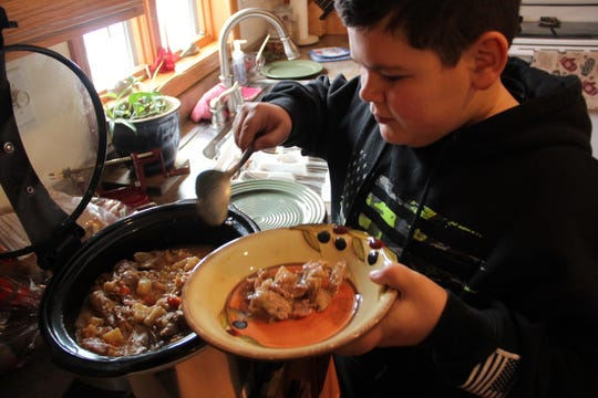 Blake Lawrence, 12, of Benton, Wis. serves up rabbit stew at a post-hunt lunch in the home of Mark LaBarbera in Hazel Green, Wis.