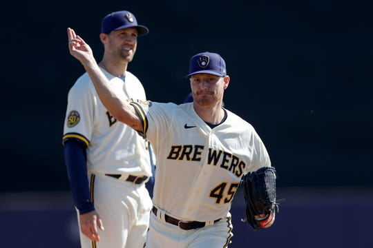 Brewers pitcher Shelby Miller  takes part in a spring training drill drill with pitcher Josh Lindblom Thursday.