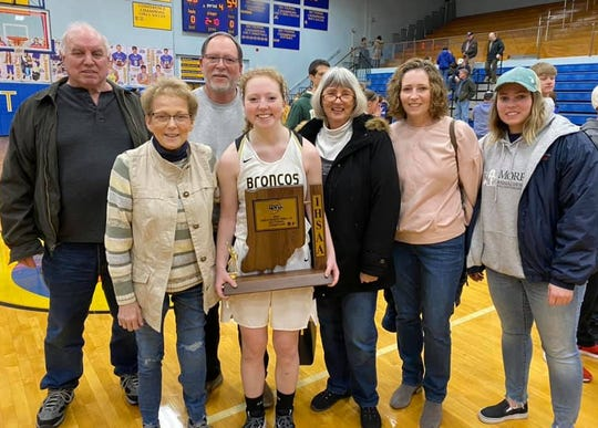 Daleville's Ashlyn Craig poses for a picture with her family after winning the first-ever Daleville girls basketball sectional championship.