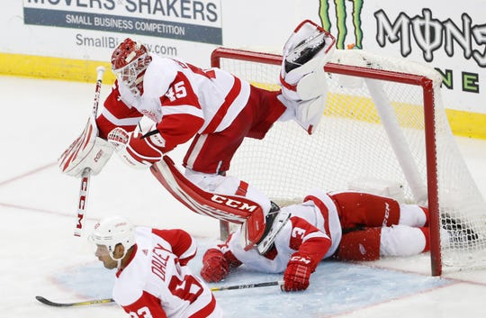 Detroit Red Wings goaltender Jonathan Bernier (45) flips over Detroit Red Wings defenseman Alex Biega (3) after Biega was shoved into the net during the third period of an NHL hockey game, Thursday, Feb. 13, 2020, in Newark, N.J. Detroit Red Wings defenseman Trevor Daley (83) skates away.
