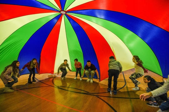 A group of fifth graders play with a parachute with Physical Education teacher Andrew Rose (center) during Global School Play Day at Woodside Avenue Elementary School in Franklin Lakes on Friday February 14, 2020. Global Play Day was started by educators to bring awareness to the decreasing amount of play in children's days.