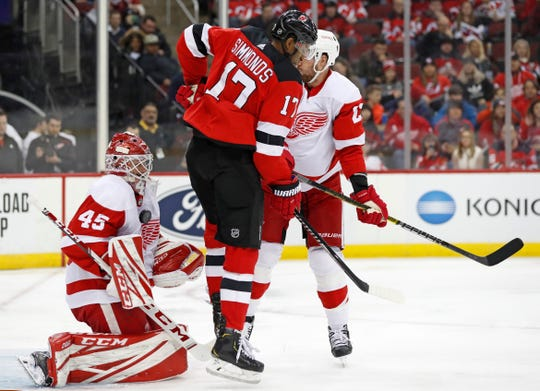 New Jersey Devils right wing Wayne Simmonds (17) leaps to allow the puck a path to the goal as Detroit Red Wings goaltender Jonathan Bernier (45) makes a save against his chest during the second period of an NHL hockey game, Thursday, Feb. 13, 2020, in Newark, N.J.