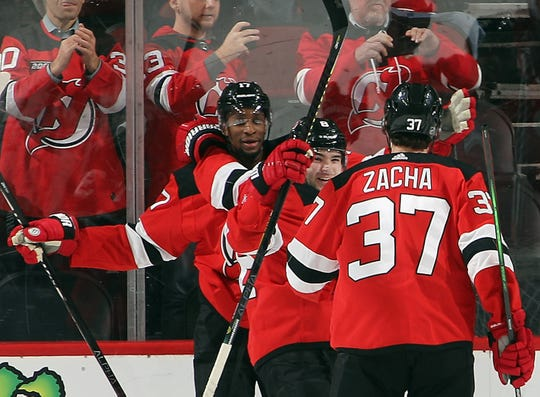 Wayne Simmonds #17 of the New Jersey Devils (L) celebrates his goal at 6:54 of the third period against the Detroit Red Wings and is joined by Will Butcher #8 (C) and Pavel Zacha #37 (R) at the Prudential Center on February 13, 2020 in Newark, New Jersey.