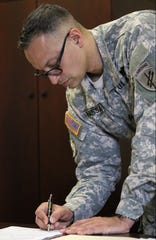 Sgt. Syed Farhaj Hassan is shown at Fort Dix as he signs his reenlistment papers, Monday April 16, 2018.