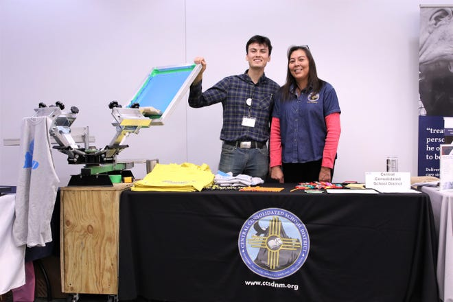 Print Shop Technician at Central Consolidated School District, Jerrod Noble, left, and Human Resource Specialist at CCSD Melinda Lynn Farley, showed off their screen printing machine at San Juan College's Career & Internship Fair at the Henderson Fine Arts Center Performance Hall on Feb. 13, 2020.