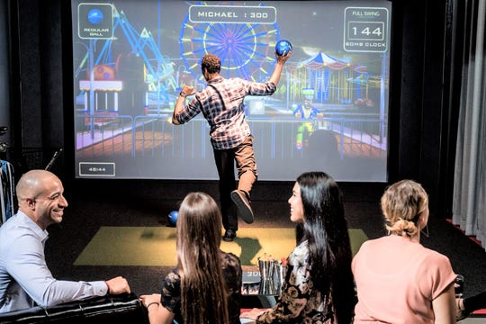 Topgolf Swing Suite, featuring two simulator bays, comfortable lounge seating and food and beverage service.