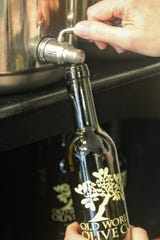 A bottle is filled with balsamic vinegar at the Old World Olive Company in downtown Plymouth.