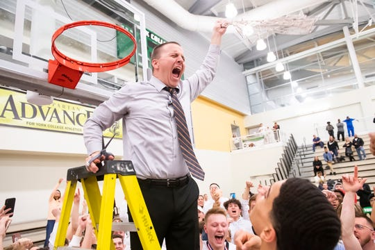 Central York head coach Kevin Schieler swings the net after cutting it down during the postgame celebration in Charles Wolf Gym at York College Thursday, Feb. 13, 2020. The Panthers defeated New Oxford 42-32 to claim the YAIAA title.