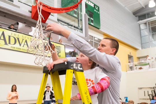 Central York head coach Kevin Schieler, joined by his daughter, Emma, cuts down a piece of the net during the postgame celebration in Charles Wolf Gym at York College Thursday, Feb. 13, 2020.
