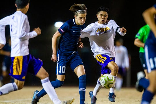 Perry forward Kyle Brereton and Mesa midfielder Brayan Susano fight for the ball during a high school soccer game between Mesa and Perry High Schools at Perry on Thursday, Feb. 13, 2020.