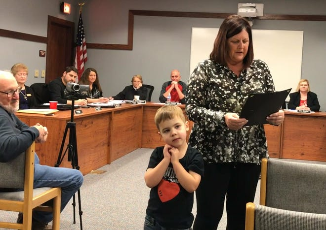 """Lucas Gutman, 4, listens along as Port Clinton City Council President Lisa Sarty reads an official proclamation from the city recognizing """"Conquering Congenital Heart Defect Week."""""""