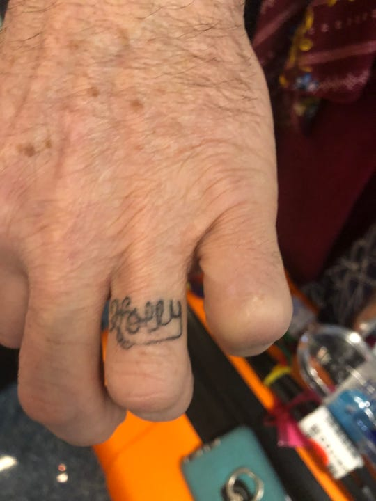 """John """"Jack"""" Uberti has the name of his future wife, Holly Chickos, tattooed on his ring finger. The couple advantage of the pop-up marriage office at McCarran International Airport Thursday afternoon."""
