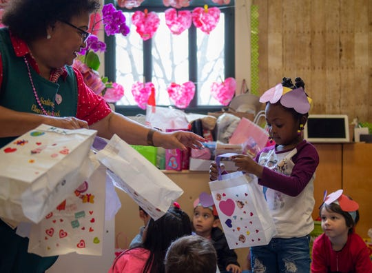 Yolanda Cabrera, associate pre-school teacher hands a young girl a Valentine's Day bag. The kids made these bags so they can put the goodies that their classmates will be giving out throughout the day on Feb. 14, 2020.
