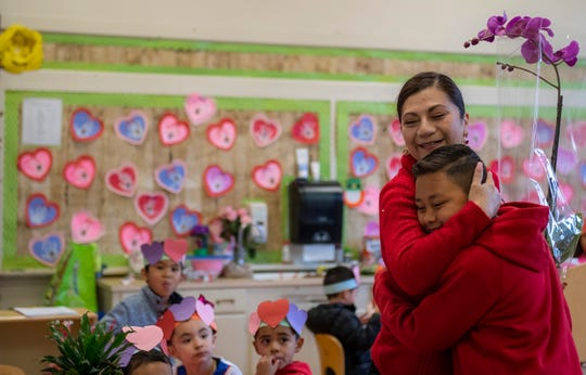 "Alijah'Kai Martinez, 9, fourth-grade hugs his former pre-school teacher Ms. Razo as he hands her a purple orchid for Valentine's Day. ""I get to deliver flowers to all my teachers that I've had so far,"" said Martinez. ""I like to see the reaction in their faces when I give them their gifts."