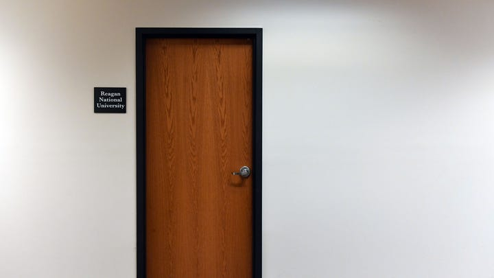 A sign for Reagan National University is posted outside one of two locked doors in the office building at 114 S. Main Ave on Wednesday, Jan. 29, in downtown Sioux Falls.