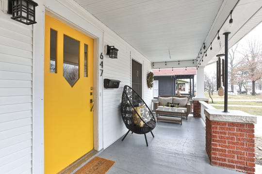 """Jen opted to inject a brilliant shot of color on the front porch with this cheery yellow. """"I knew I wanted a bold color, but I didn't want anything typical,"""" she says."""