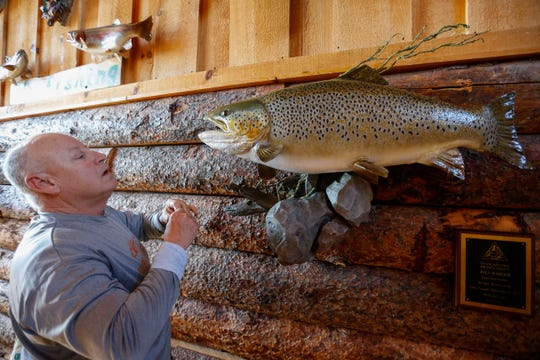 Bill Babler looks to show where he hooked the record setting brown trout in Lake Taneycomo last year.