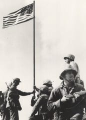 """Monticello native Earnest """"Boots"""" Thomas, sitting in the foreground holding a rifle, was part of the first unit photographed raising a flag after the battle of Iwo Jima. Thomas was killed eight days later, a week short of his 21st birthday."""