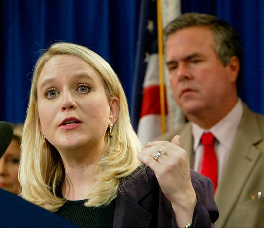 In this Tuesday, Sept. 28, 2004, file photo, Tiffany Carr, executive director of Florida Coalition Against Domestic Violence, left, speaks at a news conference held by Gov. Jeb Bush, background right, to announce a public awareness campaign designed to prevent disaster-related domestic violence, in Tallahassee, Fla. On Thursday, Feb. 13, 2020, Florida Gov. Ron DeSantis ordered an investigation into a nonprofit domestic abuse agency whose CEO, Carr, had received $7.5 million in compensation over a three-year span.