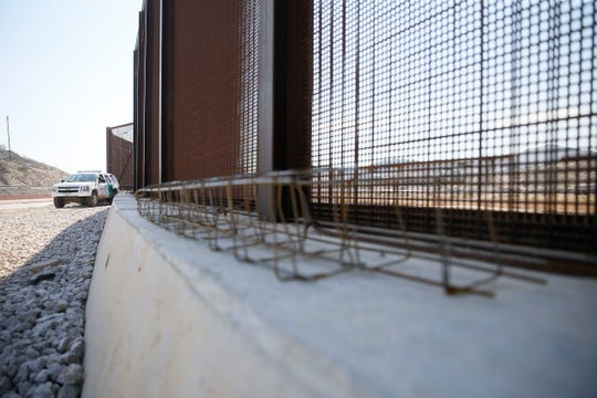 Border patrol agents Joe Romero and Fidel Baca look at discarded ladders migrants use to climb over the border fence Thursday, Feb. 13, in El Paso.