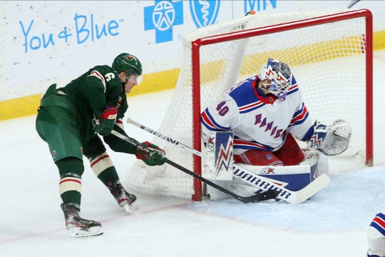New York Rangers goalie Alexandar Georgiev, right, stops a shot by Minnesota Wild's Ryan Donato during the first period of an NHL hockey game Thursday, Feb. 13, 2020, in St. Paul, Minn.