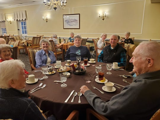Friends gather at Millcroft senior living community to share some laughs over a meal.