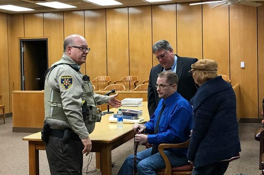 William Edward Dillard Muirhead, 49, seated,  is about to be led from 78th District Court to Wichita County Jail. His mother, Carol Dillard Muirhead, is to the right, and his lawyer, Greg Merkle, is behind him. The Wichita County law-enforcement officer shown took him to the jail.