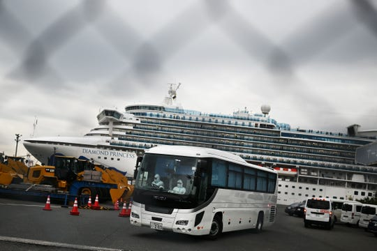 A bus driven by a chauffeur in protective gear departs the dock occupied by the quarantined Diamond Princess.  A group of passengers who are elderly or have pre-existing medical conditions were removed from the ship Friday and will finish out their quarantine on shore in Japan.