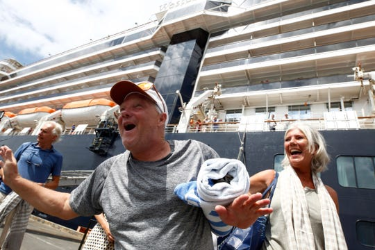 Passengers react after disembarking from Holland America's MS Westerdam, at the port of Sihanoukville, Cambodia, Friday, Feb. 14, 2020. Hundreds of cruise ship passengers were stranded at sea by coronavirus fears, and the ship was denied entry to multiple ports despite not having any cases of the virus on board.