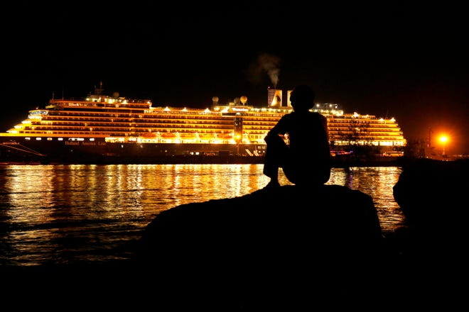 A man watches the MS Westerdam, owned by Holland America Line, anchored off the port of Sihanoukville, Cambodia, early Friday. Hundreds of cruise ship passengers long stranded at sea by virus fears cheered as they finally disembarked later in the day and were welcomed to Cambodia.