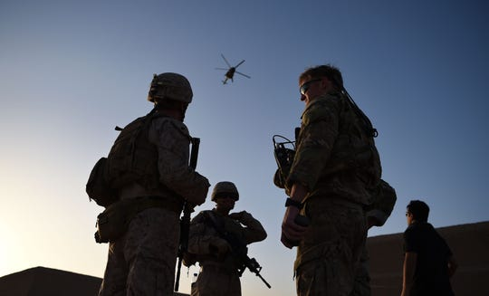 U.S. Marines and Afghan Commandos stand together as an Afghan Air Force helicopter flies past during a combat training exercise at Shorab Military Camp in Lashkar Gah in Helmand province.