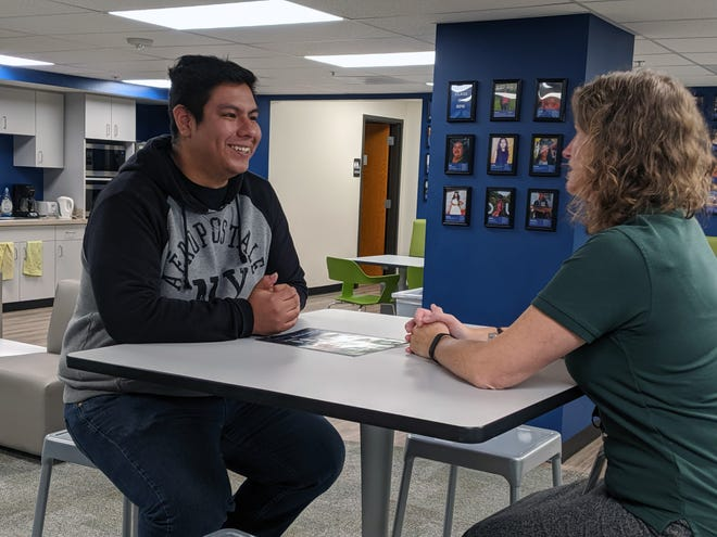 Emmanuel Villagomez talks about a new, better-paying job with Kelly Schaer, the director of College Possible, an organization that provides support to low-income college-bound students in Milwaukee. He pays $500 a month toward his student debt.