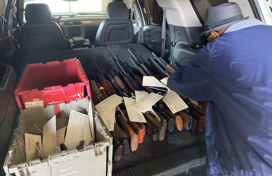 More guns are placed into the back of a sports-utility vehicle on Saturday during the city of Alexandria's gun buyback program.