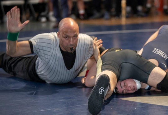 Referee Ron Roberts (upper left) slaps the mat after Southern's Cole Velardi (forefront) pins Nick Acque to give Southern a 36-30 win over Howell in the NJSIAA South Group V championship match.