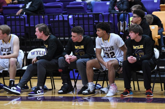 Conner Ruffin, Avery Brekke, Payton Brooks and Reed Hughes look on with injuries from the Wylie bench against No. 17 Wichita Falls Rider at Bulldog Gym on Friday. Ruffin, Brekke and Hughes had injuries coming into the game and Brooks was injured early in the 44-38 loss.