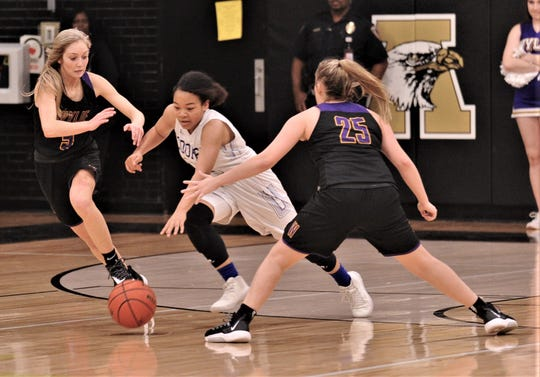 Cooper's Kyla Speights, center, dribbles the ball between Wylie's Morgan Travis, left, and Makinlee Bacon in the second half. Cooper beat the Lady Bulldogs 46-42 in the District 4-5A seeding game for the No. 3 seed Friday, Feb. 14, 2020, at Abilene High's Eagle Gym.