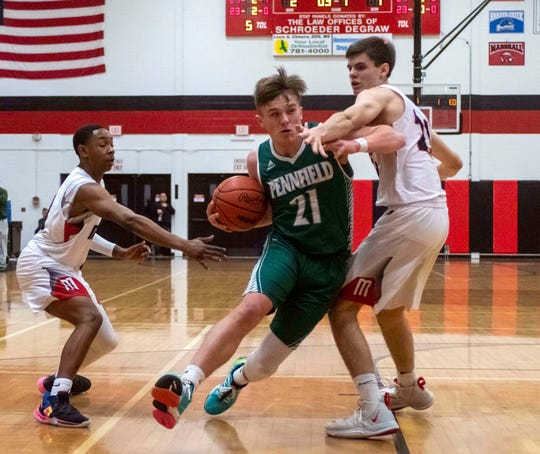 Pennfield's Shawn Gardner (21) drives the basket as he tries for two points during game action Friday night as the Panthers face off against the Marshall Redhawks.