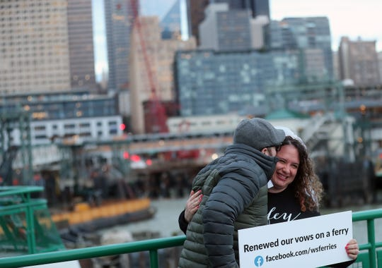 Brian Lichtman kisses his wife Laura as they pose for a photo on the bow of the the Washington State Ferry Tacoma as it heads from Bainbridge Island to Seattle's Coleman Dock on Friday, Feb. 14, 2020. Married for 15 years, the Lichtman's renewed their vows aboard the ferry with a handful of other couples in celebration of Valentine's Day.