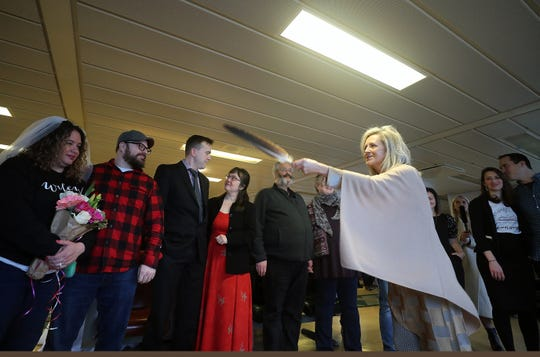 Grace MacLeod waves an eagle feather over the couples as she officiates their vow renewal ceremony aboard the Washington State Ferry Tacoma en route from Bainbridge Island to Seattle on Friday, Feb. 14, 2020.