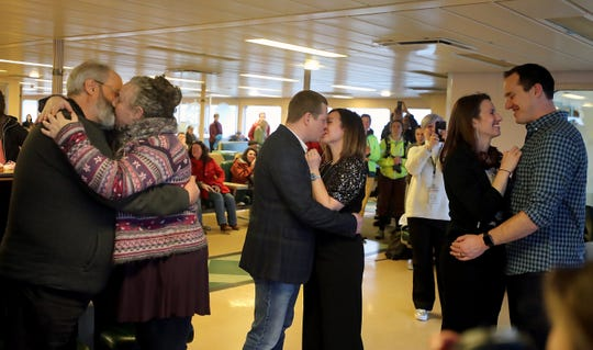 Robert Orr and wife Marni Rachmiel, of Seattle (left) and Vasilii and Julia Aramilev, of Lynwood, (center) kiss at the conclusion of their vow renewal ceremony aboard the Washington State Ferry Tacoma en route from Bainbridge Island to Seattle on Friday, Feb. 14, 2020. Orr and Rachmiel have been married for 12 days while the Aramilev's were renewing their vows after 15 years.