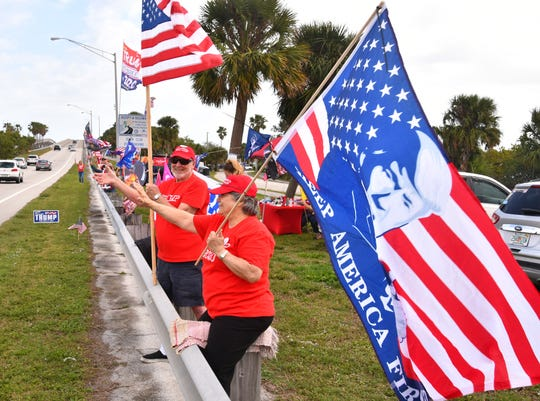 A group of pro-Trump counter-protesters waved and displayed more than 25 flags to passing traffic near the park entrance.